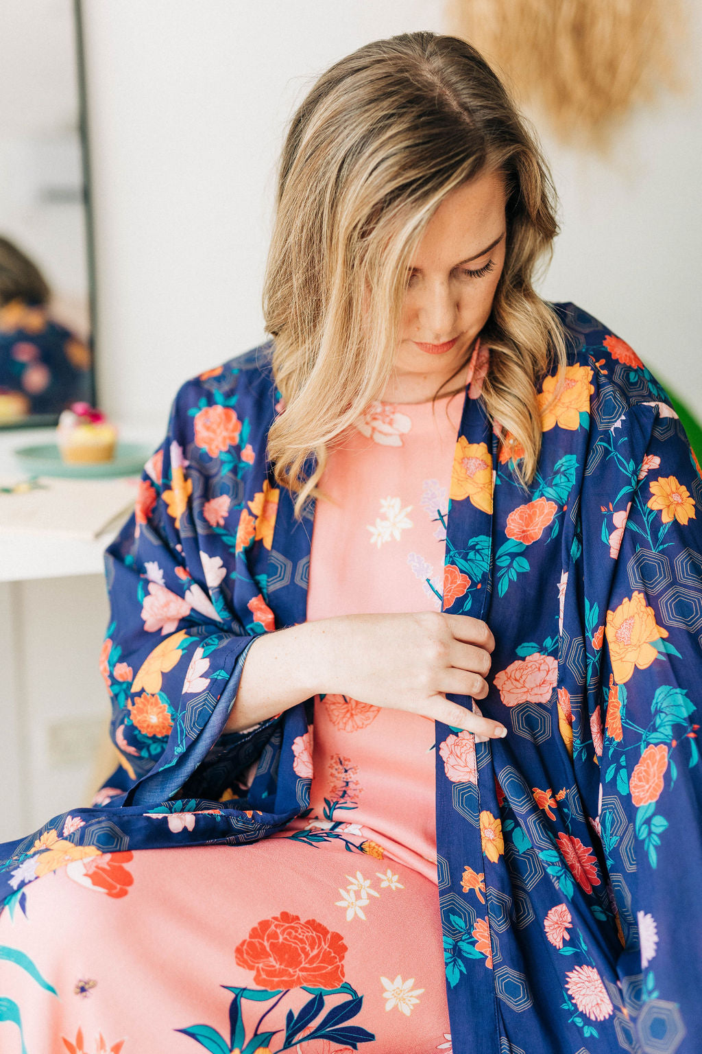 woman looking at the sleeve of her limonata navy floral print chimono robe