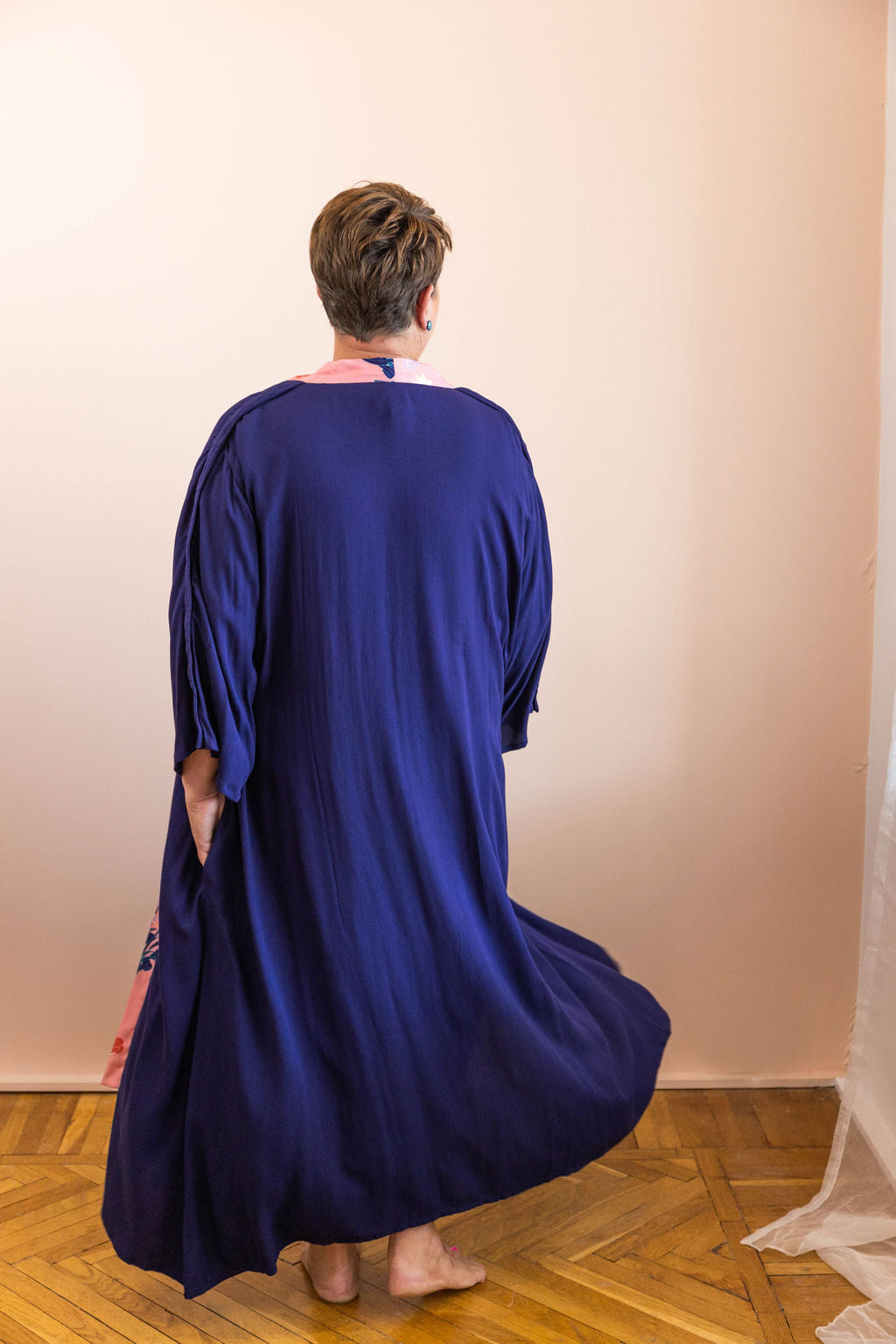 woman twirling in navy adaptive dressing gown