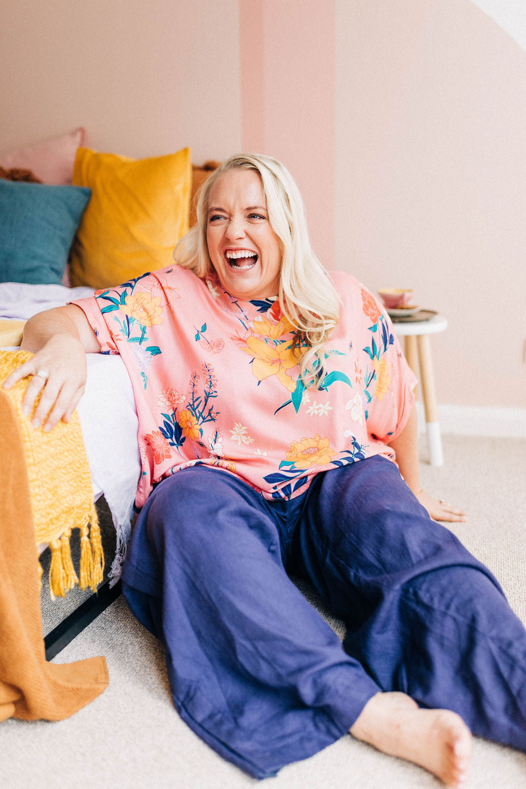 woman laughing, leaning against a bed and wearing a pink floral adaptive top and navy linen adaptive pants