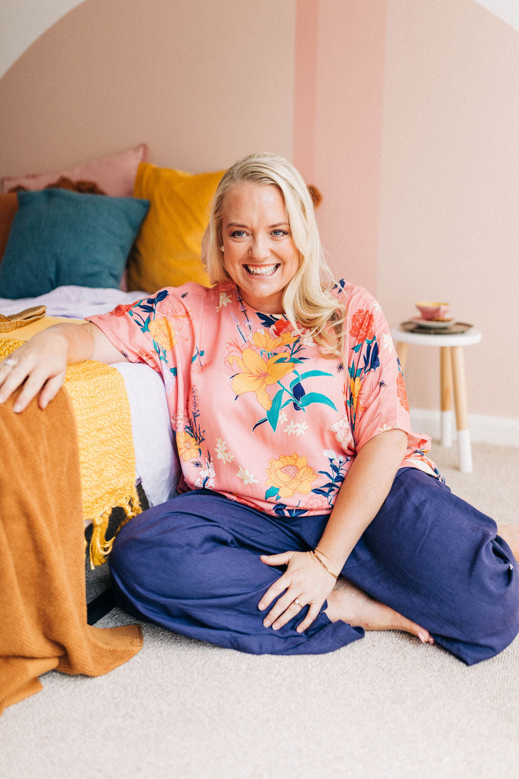 smiling woman sitting comfortably on the floor wearing a pink floral adaptive top and adaptive linen pants in navy
