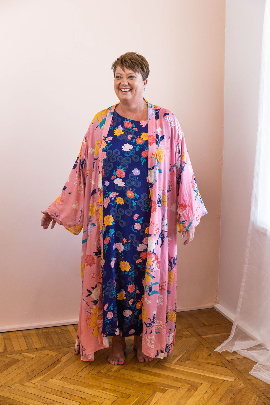 woman wearing pink fiorella floral chimono robe with navy dress