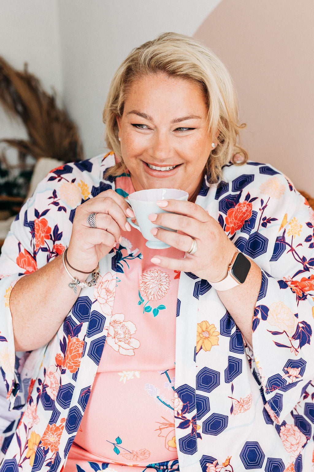 woman in bright dress and colourful adaptive dressing gown drinking a cup of tea