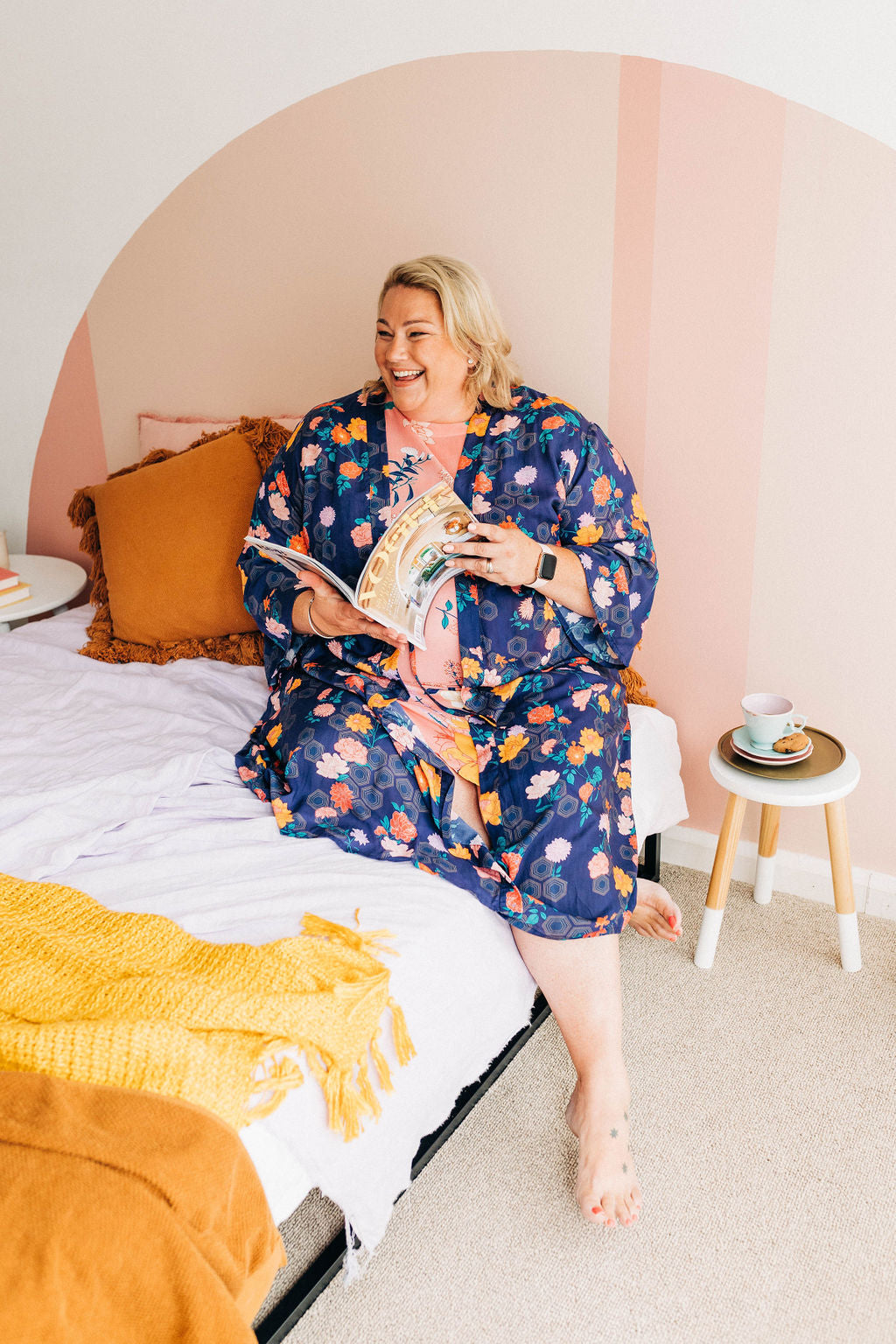 woman sitting in bed reading a magazine wearing a navy floral chimono robe
