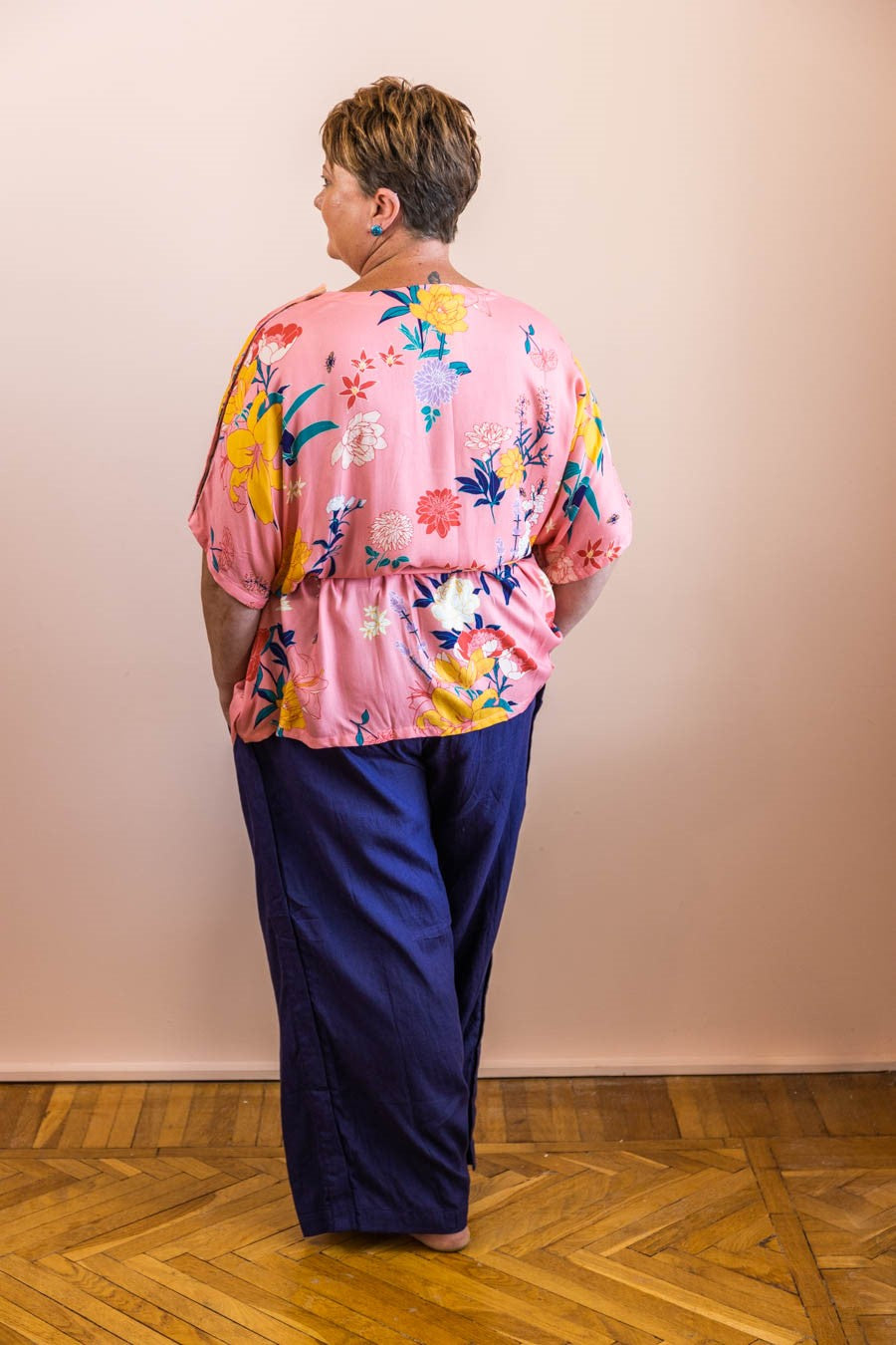 woman standing showing back view of pink floral adaptive top and navy adaptive linen pants