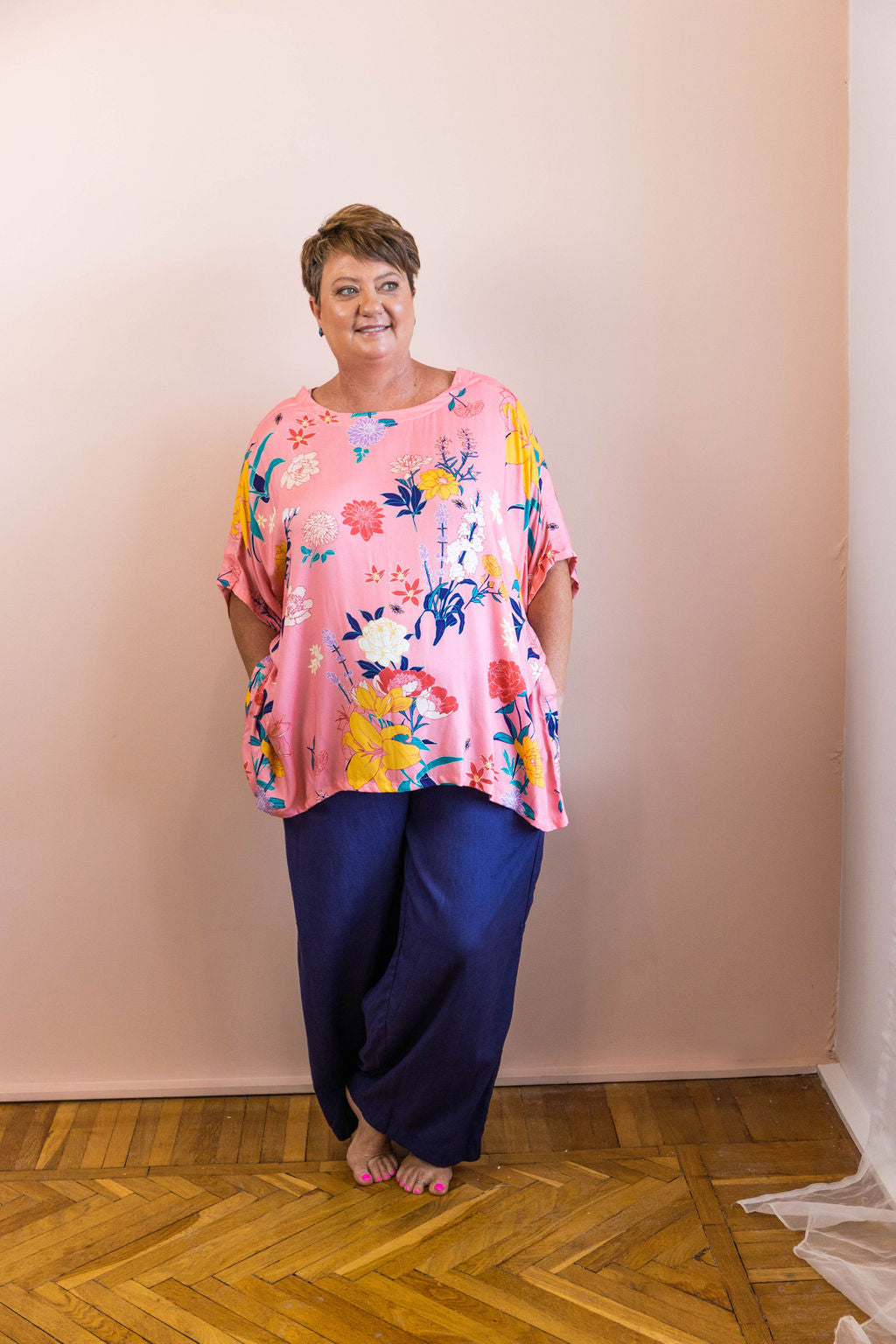 woman standing wearing pink floral fiorella adaptive top and navy linen adaptive pants