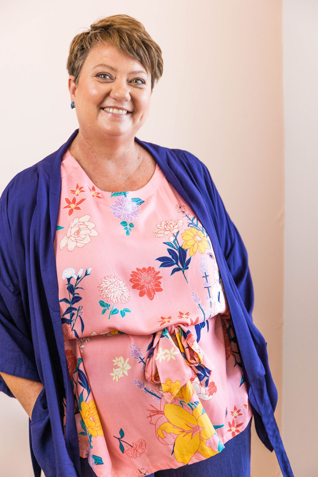 woman smiling at the camera and wearing pink floral adaptive top with navy adaptive wrap top worn as a jacket