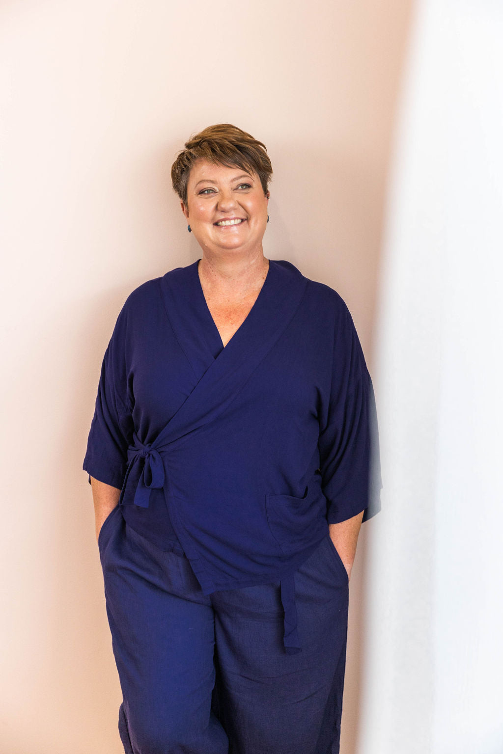 woman smiling wearing all navy limonata adaptive wrap top and linen pants