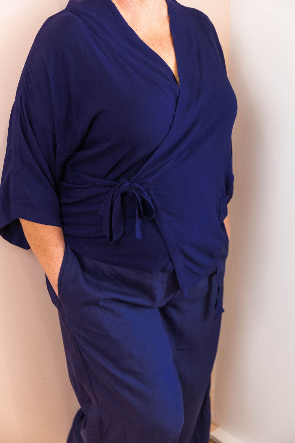 detail shot of woman wearing all navy limonata adaptive wrap top and linen pants