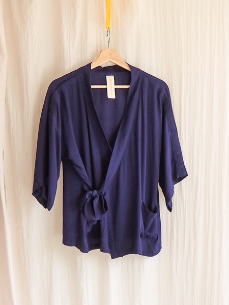 limonata navy grazia adaptive wrap top hanging on a coathanger