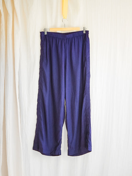 wide leg navy linen adaptive pants by limonata, hanging on a coathanger