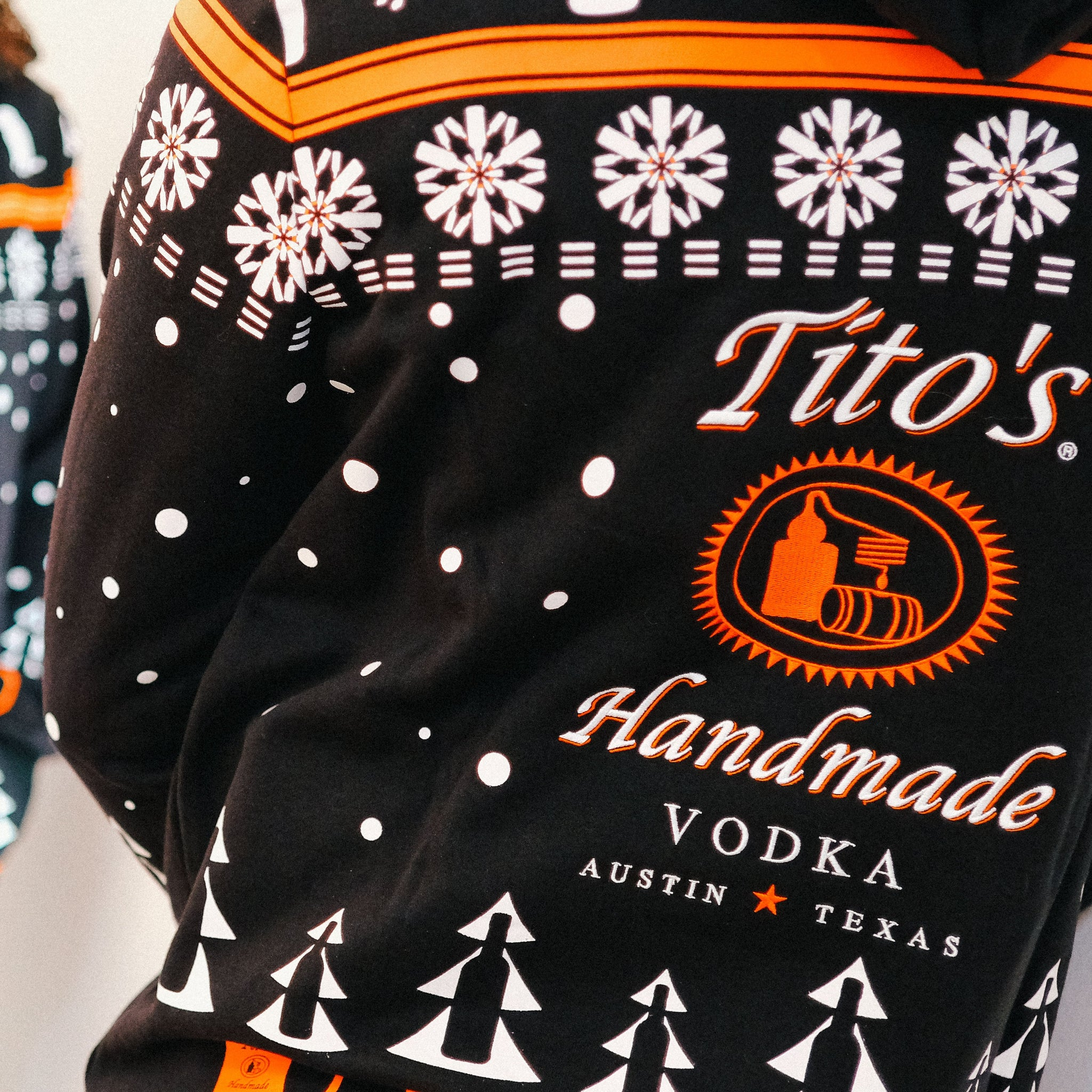 Back view of hooded sweatshirt with Tito's Handmade Vodka logo and holiday-inspired designs of snowflakes, dogs, trees, bottles, and copper mule mugs