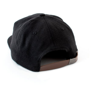 Back view of black wool hat with with brown leather adjustment