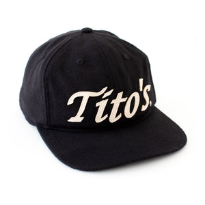 Front view of black wool hat with Tito's wordmark appliqué in creamy white felt