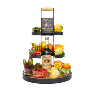 Tito's Home Bar Server filled with garnishes: olives, jalapeños, celery, pickles, tomatoes, cheese cubes, lemons, limes, and oranges