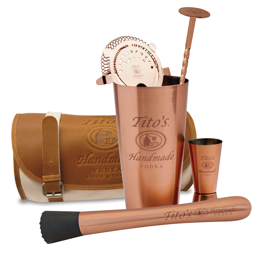 Copper mixology kit includes canvas and leather travel satchel, muddler, shaker, strainer, jigger, and bar spoon with Tito's logos