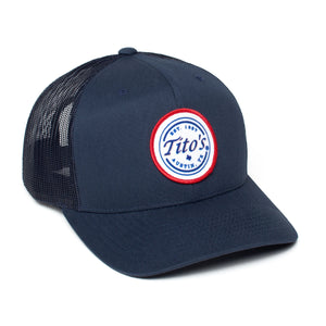 Front of navy snapback cap with red, white, and blue Tito's wordmark patch