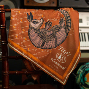 Copper silk scarf featuring white Tito's Handmade Vodka logo with illustrated armadillo and bottle designs