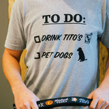 Person wearing gray short-sleeve t-shirt with To Do list, Drink Tito's, Pet Dogs on front and holding a Tito's Dog Leash