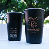 Two black Klean Kanteen pint cups with Tito's Handmade Vodka logo on a table outside