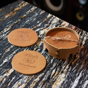 Set of leather coasters branded with Tito's Handmade Vodka logo and coaster holder