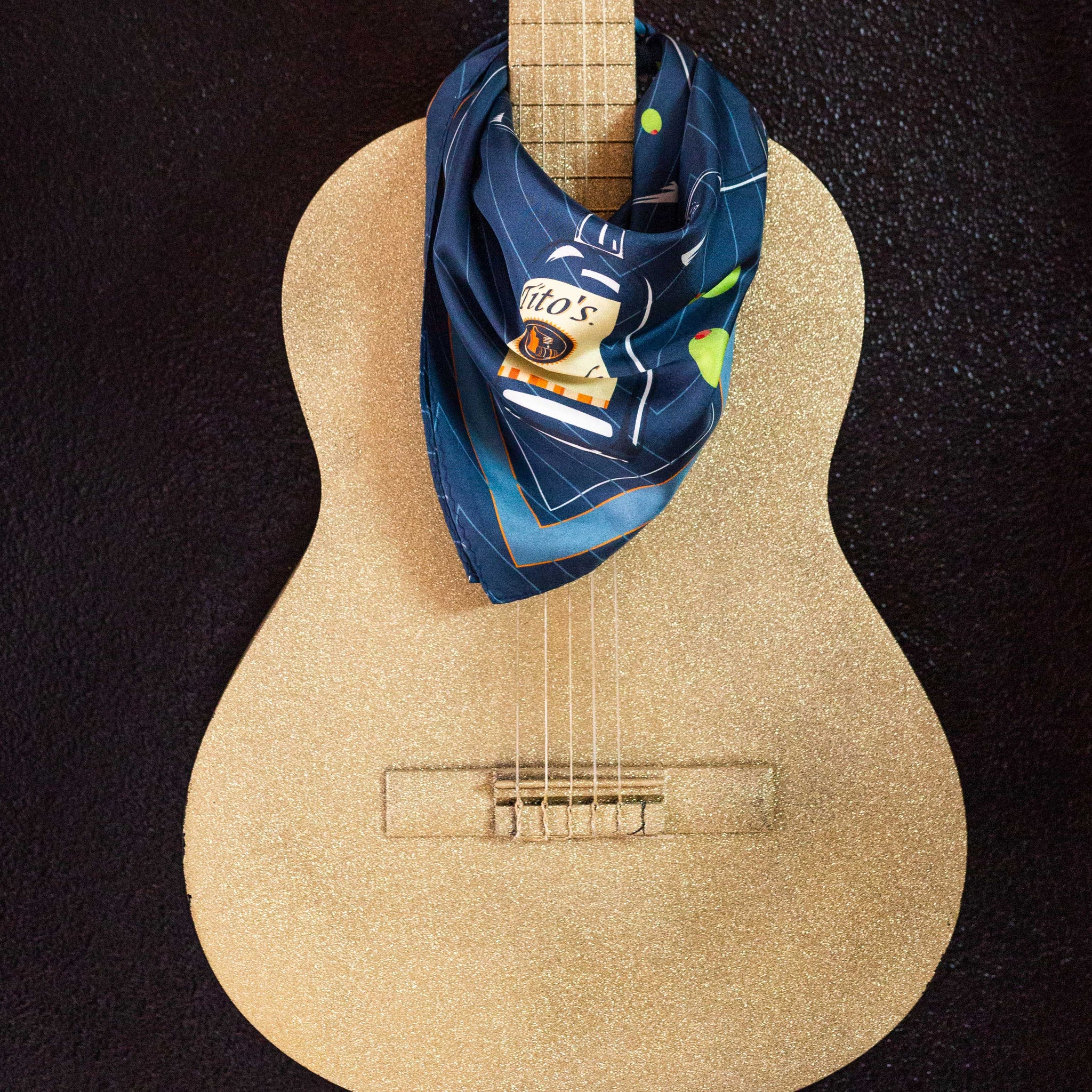 Navy Tito's Cocktail Hour Silk Scarf draped around a guitar