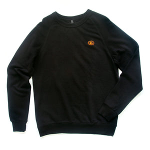 Front view of black long-sleeved pullover with embroidered orange pot still emblem on left breast