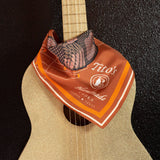 Copper Tito's Southwest Silk Scarf draped around a guitar