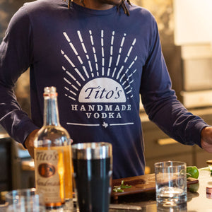 Man wearing navy long-sleeved t-shirt with Tito's Handmade Vodka mark and sunrise design