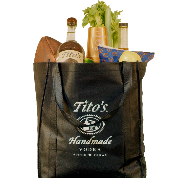 Black Tito's Tote bag filled with a Tito's Handmade Vodka bottle, football, snacks, cups and bloody mary mix