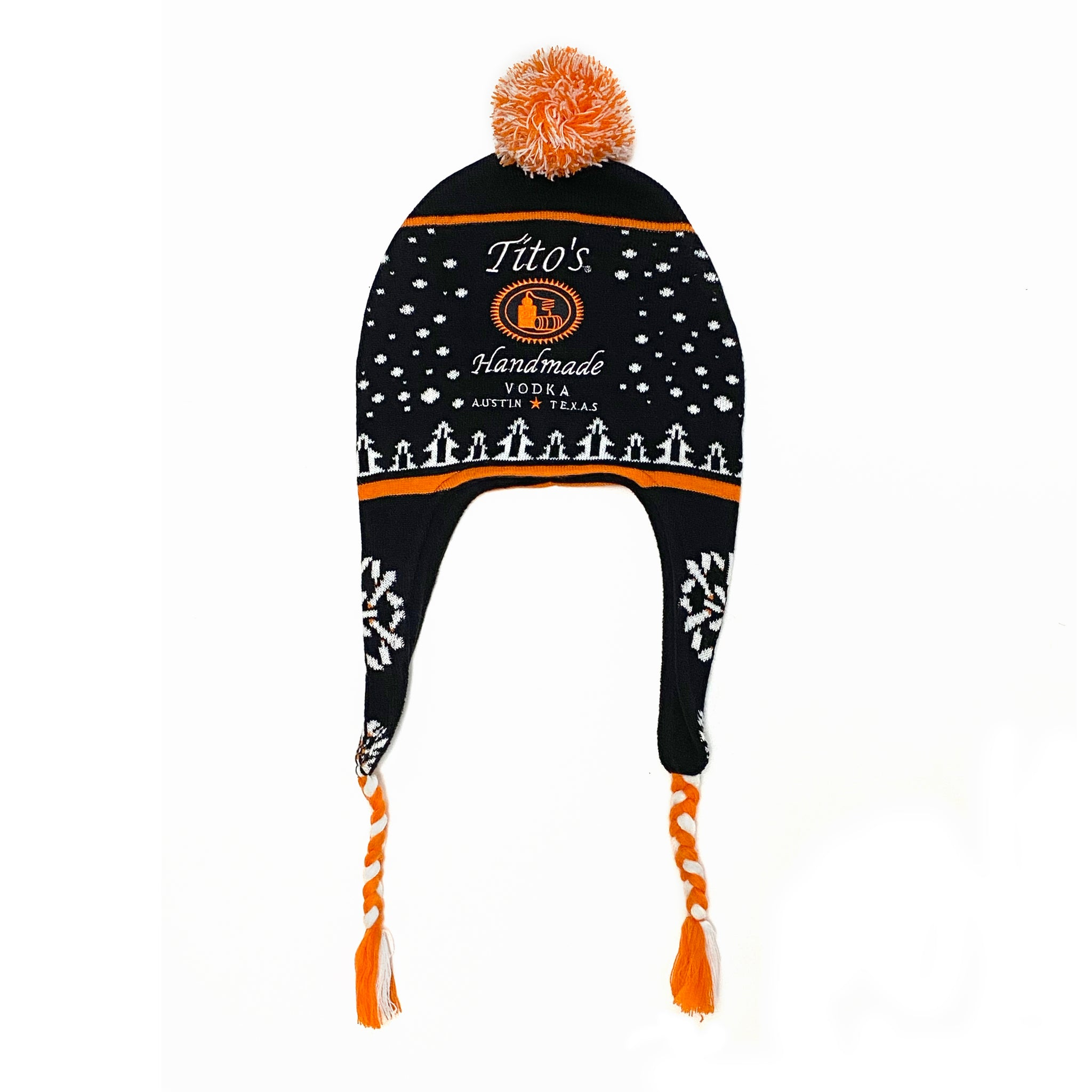 Black, orange, and white knit hat with Tito's Handmade Vodka logo and holiday-inspired designs of snowflakes, trees, and bottles, featuring orange and white braided tassels on both ends and an orange and white pom-pom on top
