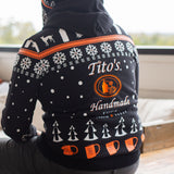 Man wearing hooded sweatshirt with Tito's Handmade Vodka logo and holiday-inspired designs of snowflakes, dogs, trees, bottles, and copper mule mugs