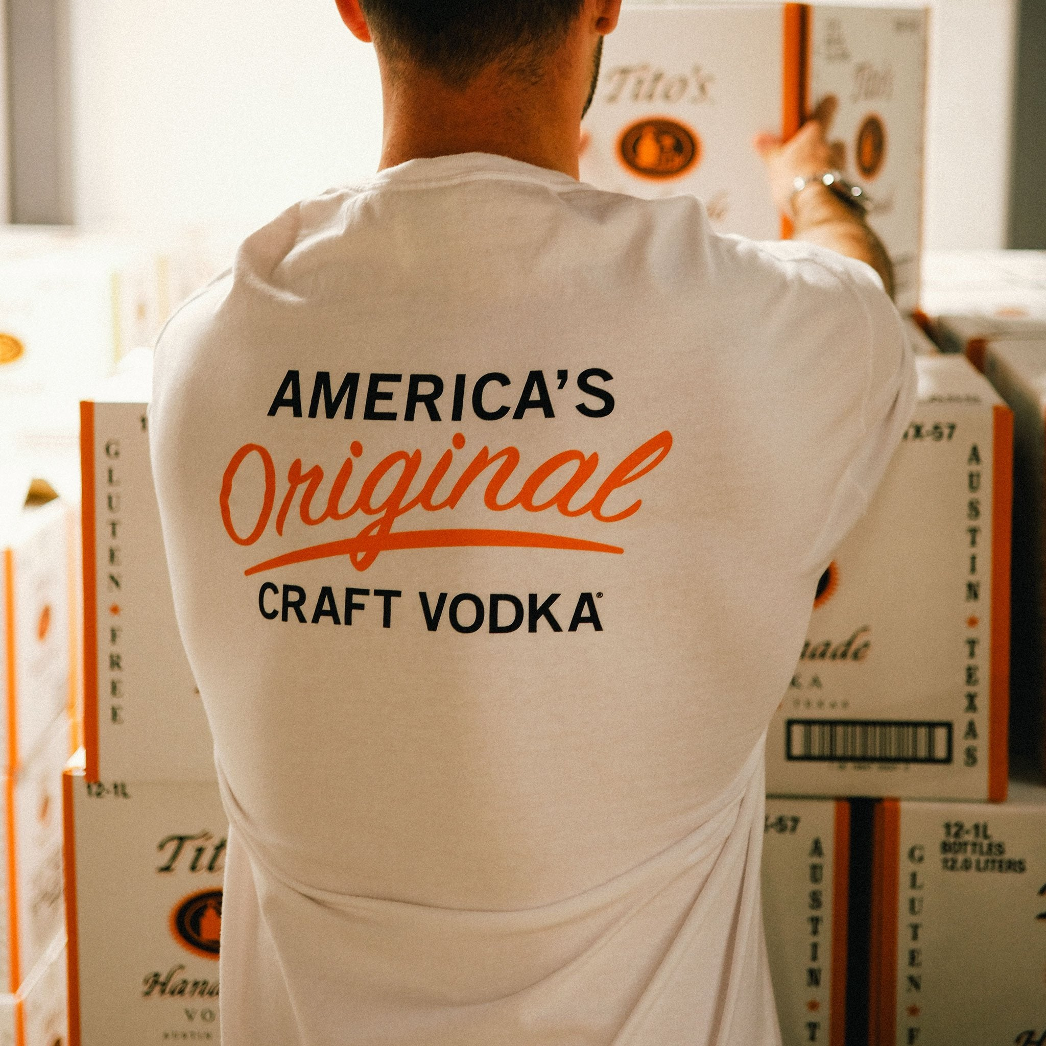 Back of person wearing short-sleeve white t-shirt with America's Original Craft Vodka mark