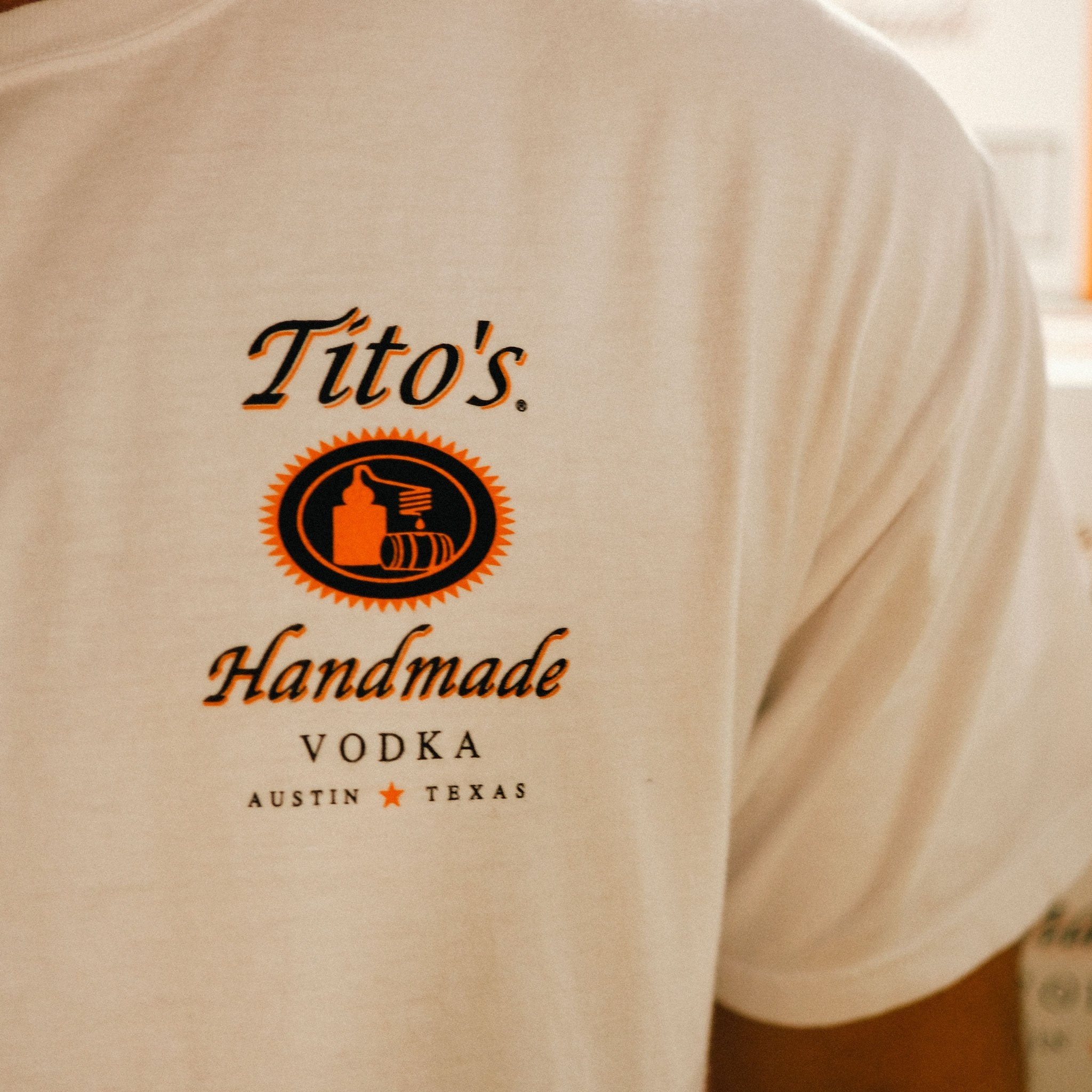 Front left breast of short-sleeve white t-shirt with Tito's Handmade Vodka logo
