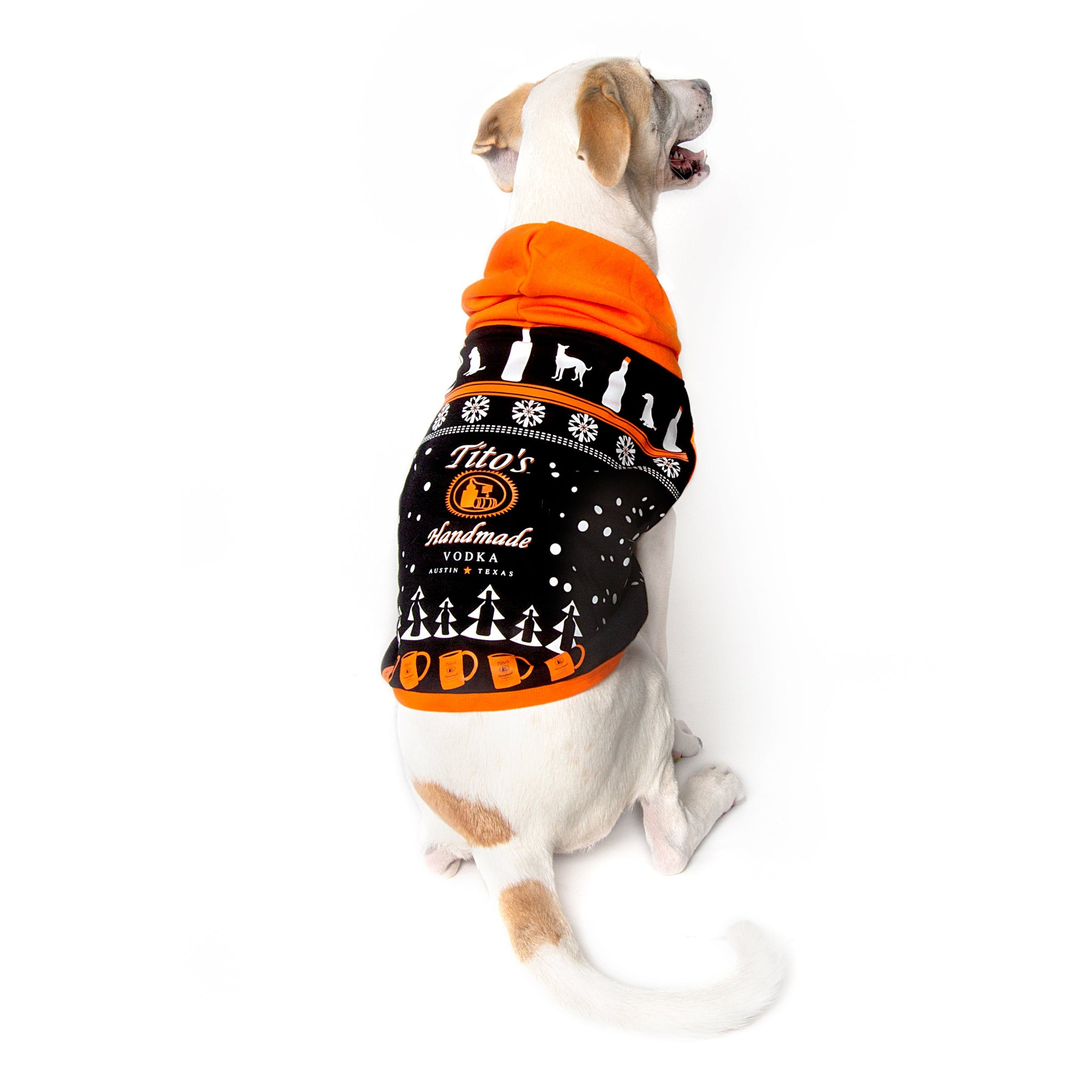 Dog wearing black, orange, and white hooded dog sweatshirt with Tito's Handmade Vodka logo and holiday-inspired designs of dogs, trees, snowflakes, bottles, and copper mule mugs
