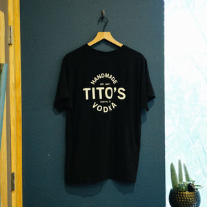 Back of black short-sleeved t-shirt with large design of Tito's Handmade Vodka, est. 1997, and Austin, TX on a hanger