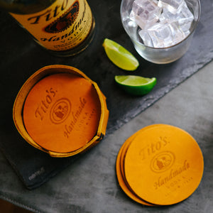 Set of leather coasters branded with Tito's Handmade Vodka logo on a table next to leather coaster holder, limes, cocktail glass, and Tito's bottle