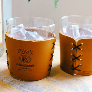 Detail view of highball cocktail glasses in leather sleeves with Tito's Handmade Vodka logo and black stitching on a table