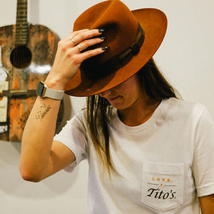 Girl wearing white short-sleeve pocket t-shirt and cowboy hat