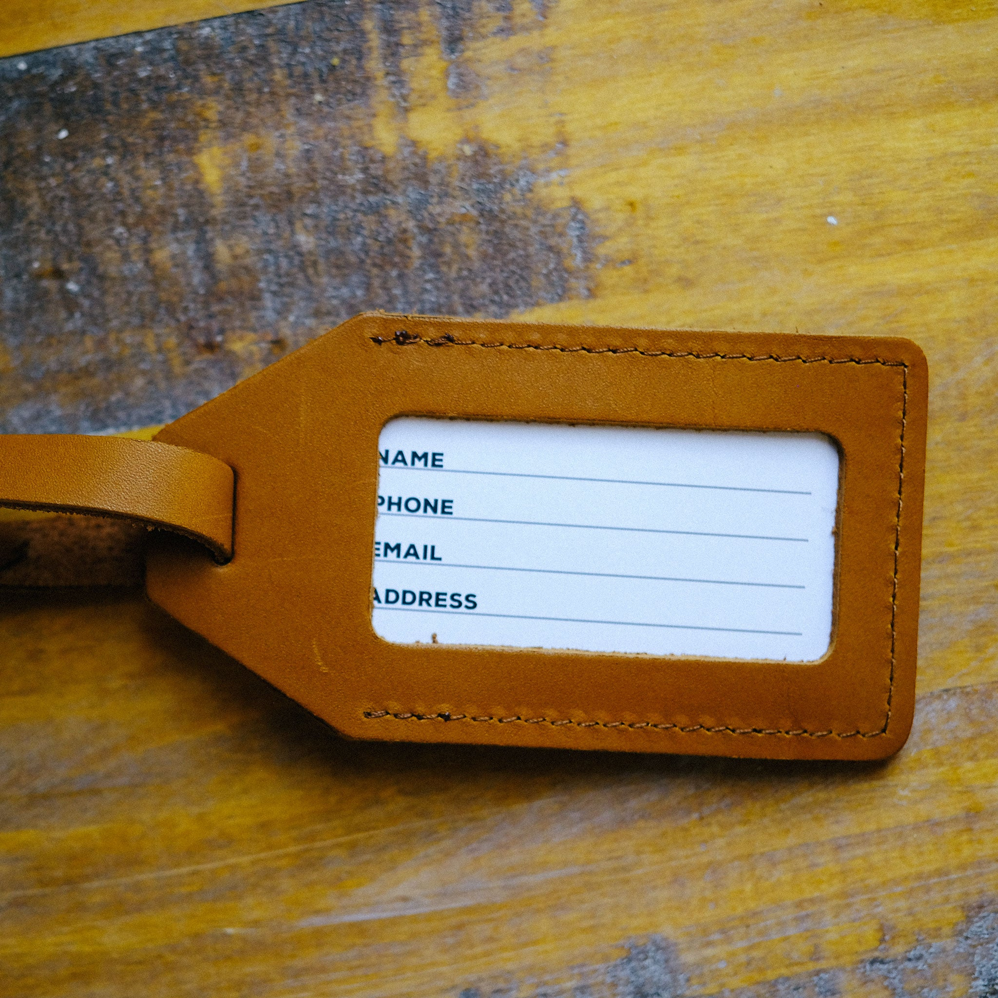 Back view of brown leather luggage tag with clear window for contact information