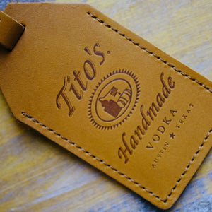 Detail view of brown leather luggage tag with Tito's Handmade Vodka logo