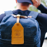 Front view of brown leather luggage tag with Tito's Handmade Vodka logo attached to a backpack