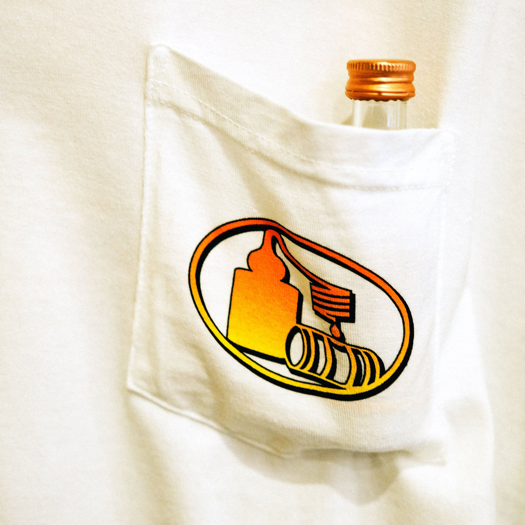 Close-up of left breast pocket with pot still design in an orange to yellow fade