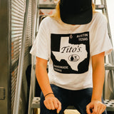 Girl sitting on stairs wearing white short-sleeve t-shirt featuring Texas state road sign design with Tito's Handmade Vodka mark