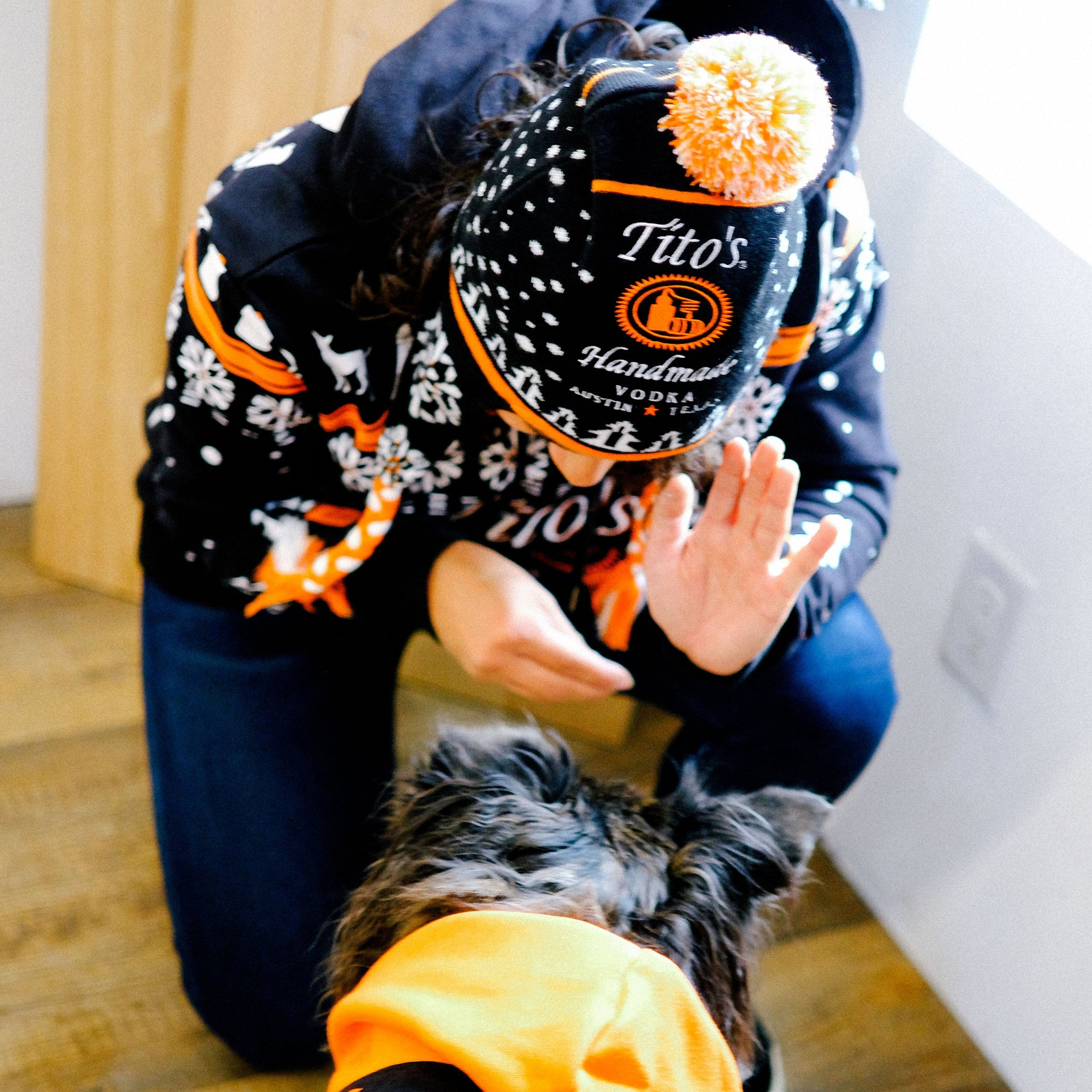 Person wearing black, orange, and white knit hat with Tito's Handmade Vodka logo.