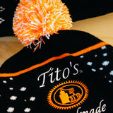 Black, orange, and white knit hat with Tito's Handmade Vodka logo. Close-up of logo and orange and white pom-pom