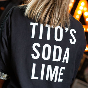 Woman wearing black long-sleeved t-shirt with Tito's Soda Lime