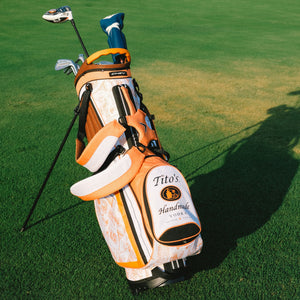 Orange and white golf bag with Tito's Handmade Vodka logo on the front and cocktail illustrations