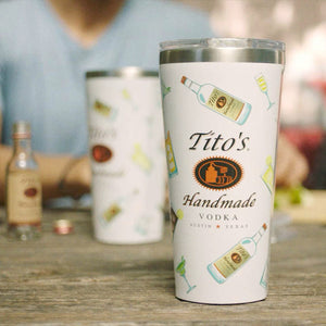White Corkcicle tumbler with Tito's Handmade Vodka logo, cocktails and Tito's bottle illustrations on a table