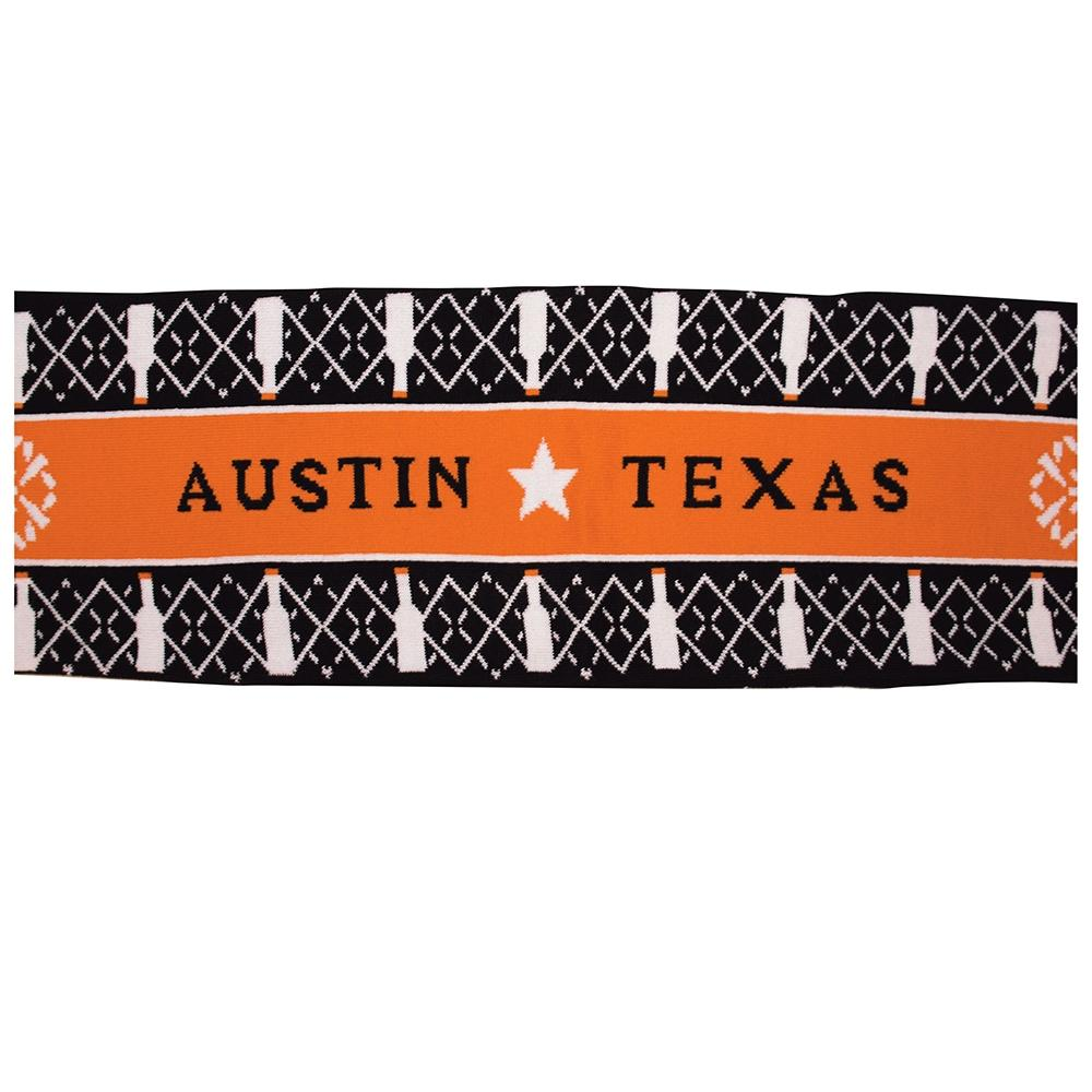 Mid-section of Tito's Ugliest Scarf features orange stripe with Austin, Texas text and Tito's bottle snowflake pattern