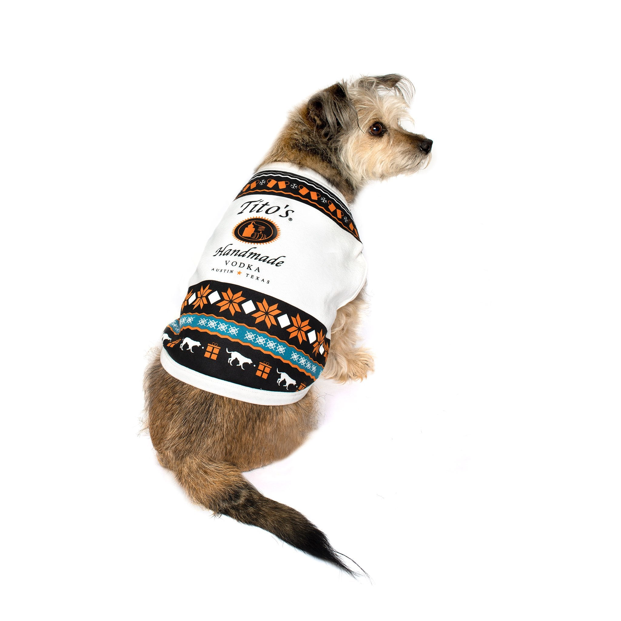 Dog wearing Tito's Ugly Dog Sweater featuring orange, blue and white holiday designs of snowflakes, dogs, and copper mugs